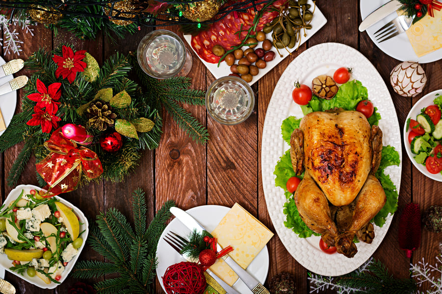 christmas-table-served-with-a-turkey-decorated-with-bright-tinsel-and-candles (1).jpeg